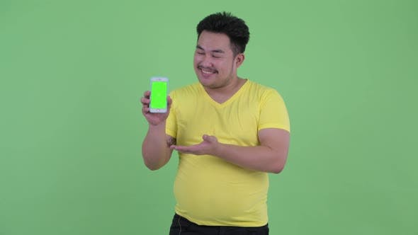 Thumbnail for Happy Young Overweight Asian Man Showing Phone and Giving Thumbs Up
