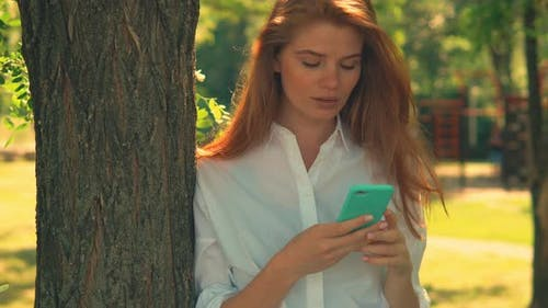 Young Woman Posing Near Tree Holding Mobile