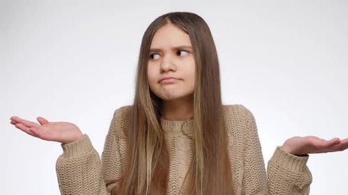 Portrait of Doubtful Girl Showing Confusion Gesture with Hands