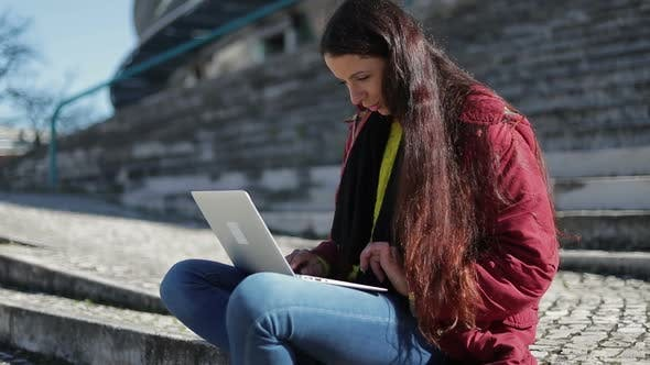 Thumbnail for Focused Mature Woman with Long Dark Hair Using Laptop Outdoor