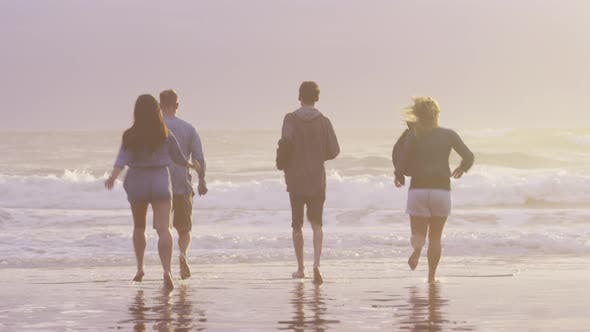Thumbnail for Group of friends at beach running in surf