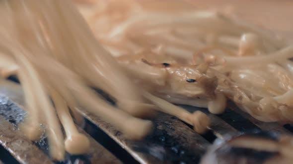 The Cook Prepares Mushrooms on Korean BBQ Gril Plate