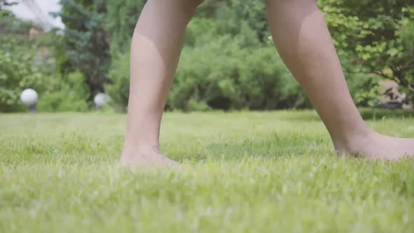 Thumbnail for Legs of the Young Woman Walking on the Grass Barefoot in the Garden