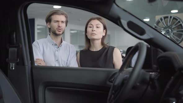 Young Confident Couple Examining New Vehicle in Car Dealership or Showroom and Talking. Portrait of