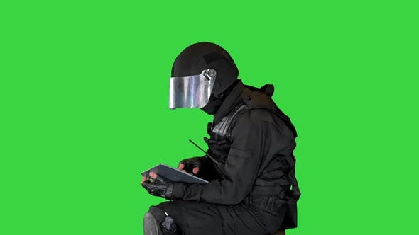 Thumbnail for SWAT Team Officer Sitting and Using Digital Tablet on a Green Screen Chroma Key
