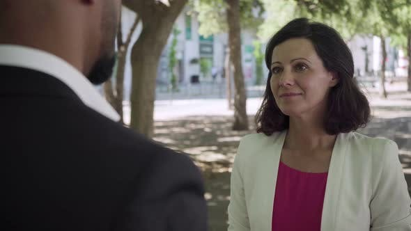 Thumbnail for Smiling Middle Aged Woman Talking with Businessman Outdoor