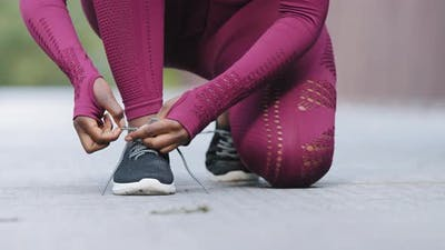 African Black Female Hands Tying Shoelace on Running Shoes Before Practice