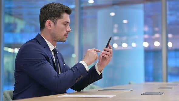 Thumbnail for Busy Businessman Using Smartphone in Office