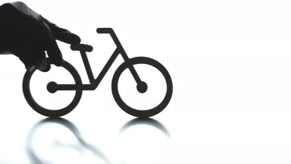 Putting Bicycle Black Icon on Light Background