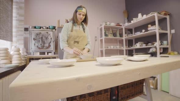Caucasian Woman Sanding Clay Bowl
