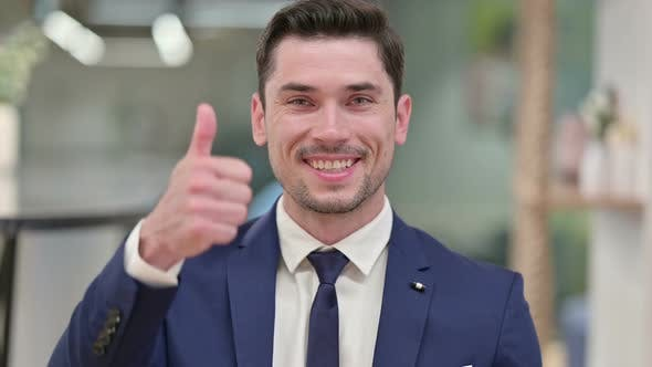 Positive Young Businessman Doing Thumbs Up