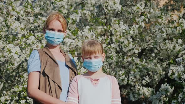 Thumbnail for Woman with Children in Gauze Bandages Against the Background of Flowering Trees. Allergy Problems in