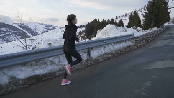 Thumbnail for Jogger in Sportswear Training in the Snowy Mountain on Sunset