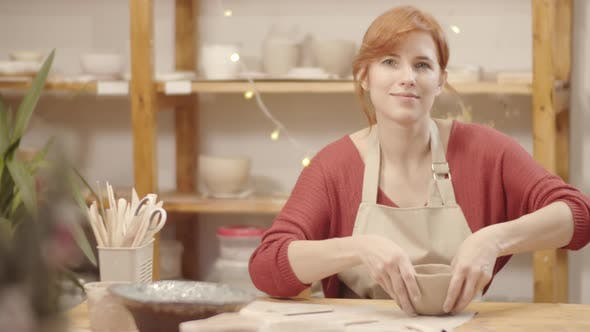 Thumbnail for Smiling Female Pottery Artist Posing in Studio while Making Clay Vessel