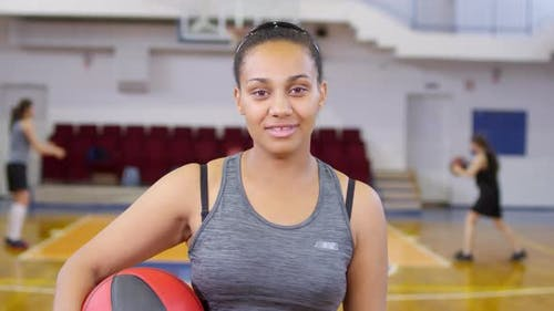 Fröhliche afrikanische Frau hält Basketball und posiert für die Kamera
