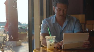 Man using tablet computer in cafe