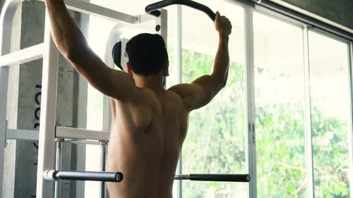 Strong Man Doing Pull Ups Exercise on Horizontal Bar at the Gym