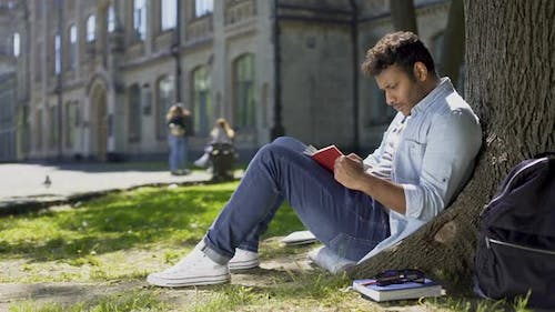 Multiracial Young Guy Sitting Under Tree, Reading Interesting Book, Bookworm