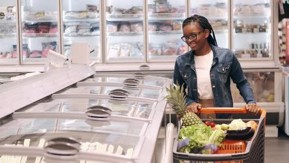 Thumbnail for African American Lady with a Shopping Cart Going Through Frozen Products Aisle
