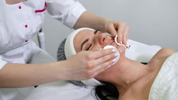 Beautician cleansing face of woman in beauty salon