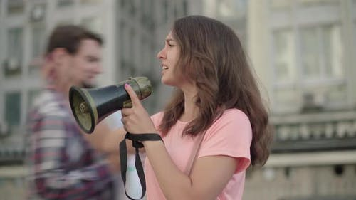 Young Eco-activist Shouting Through Megaphone and People with Banners Joining Leader in