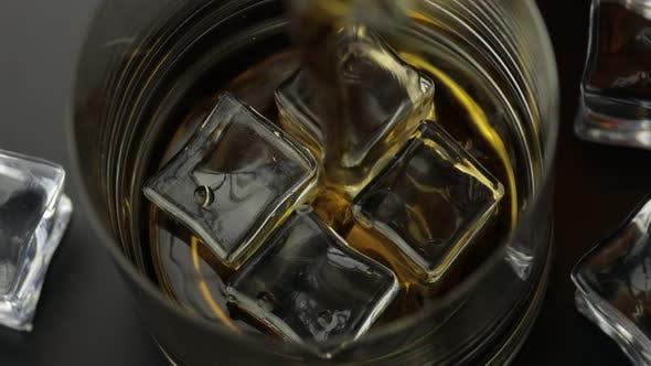 Whiskey, Cognac in Glas mit Eiswürfeln gießen. Gießen von Alkohol Getränk