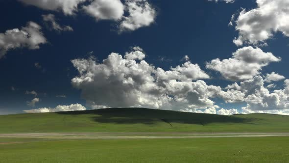 Wide Treeless Meadow Under Partly Cloudy Sky