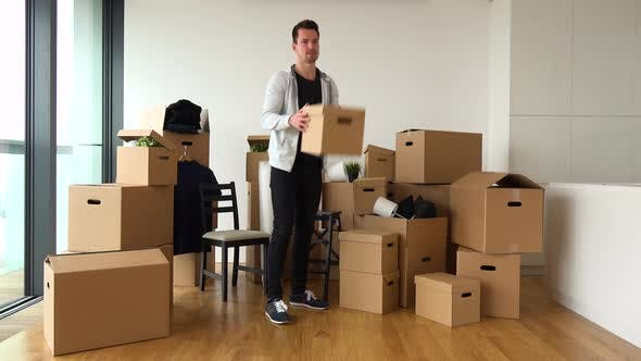 Thumbnail for A Moving Man Throws Cardboard Boxes To Someone Off the Camera in an Empty Apartment