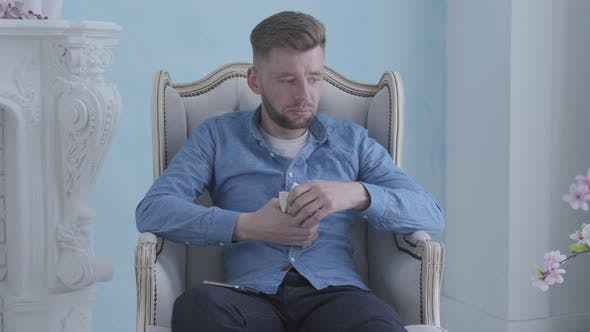 Thumbnail for Happy Thoughtful Rich Bearded Man in Blue Shirt Sitting in the White Armchair in the Light Room