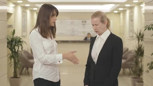 Egoistisch junge Geschäftsfrau feuert Mitte-Erwachsener Mitarbeiter im Büro. Porträt der unzufriedenen kaukasischen