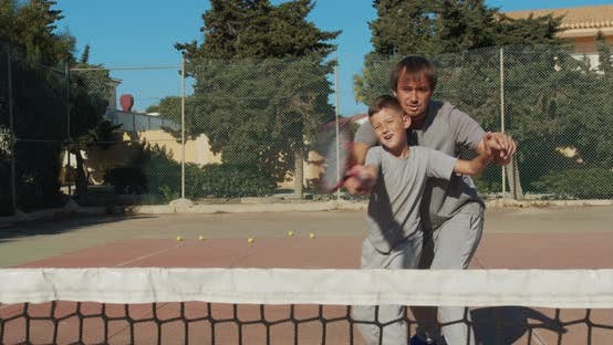 Thumbnail for Child Traning in Tennis. Father and Son Practice Blows in Tennis on Coart. Active Leisure Together.