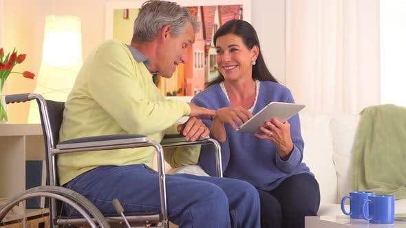 Cover Image for Happy senior coupole talking with tablet