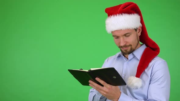 Thumbnail for A Man in a Christmas Hat Writes a Wish List Into a Notebook with a Smile - Green Screen Studio