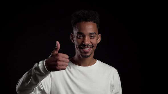 Thumbnail for Handsome Man on Black Studio Background Smiles to Camera and Gives Thumbs Up.