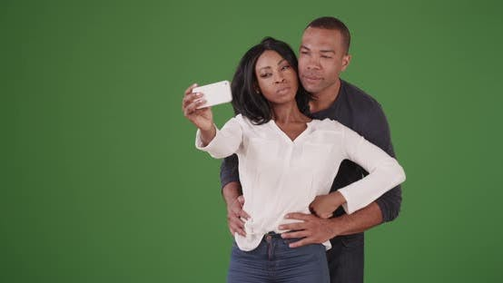Thumbnail for Black couple posing for selfies on her smart phone on green screen