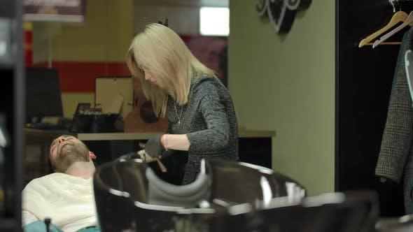 Female Professional Barber Cutting Beard Hair on Customer with Straight Razor