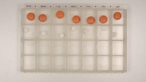 Female nurse hand puts down a pills into a pill organizer