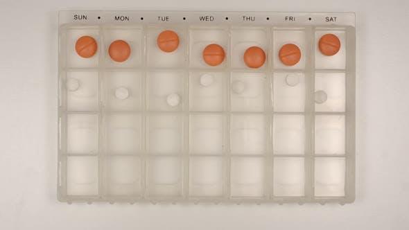 Thumbnail for Female nurse hand puts down a pills into a pill organizer