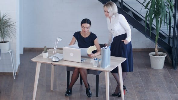 Cover Image for Two women working together with documents and laptop at office