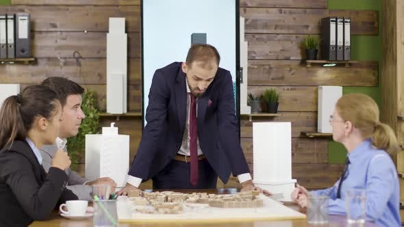 Thumbnail for Architect in Business Suit Leaning Forward the Table