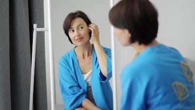 Satisfied Woman Looking at Mirror