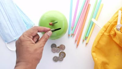 Saving Coins in a Coin Bank with Pencil and Face Mask on Table