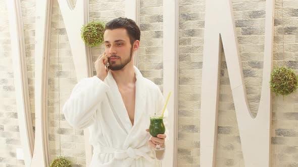 Thumbnail for Attraktiver Mann im weißen Gewand verbringt Zeit im Elite Spa Center. Telefonieren auf dem Handy und geht vorbei