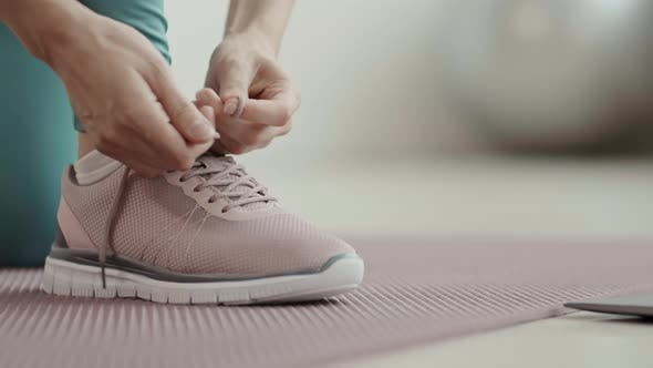 Cover Image for Woman Lacing up Sneakers