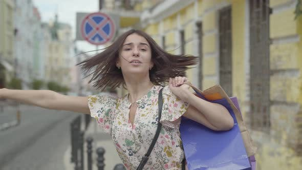 Thumbnail for Cute Young Woman Wearing Summer Dress with Shopping Bags in Hands Trying To Catch the Taxi