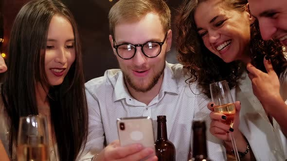 Thumbnail for Portrait Shot of Group of Happy Hipster Students Watching Video, Photo on the Smart Phone Together