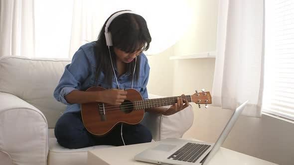 Thumbnail for Black girl singing and playing ukulele