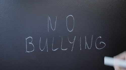 Hand writing no bullying on blackboard. Stop harassment. Human rights