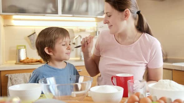 Little Boy with Mother Pouring Cream and Sugar in Bowl for Baking Cake
