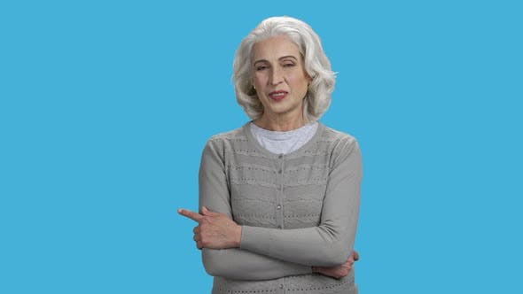 Smiling Mature Woman Pointing with Finger at Copy Space